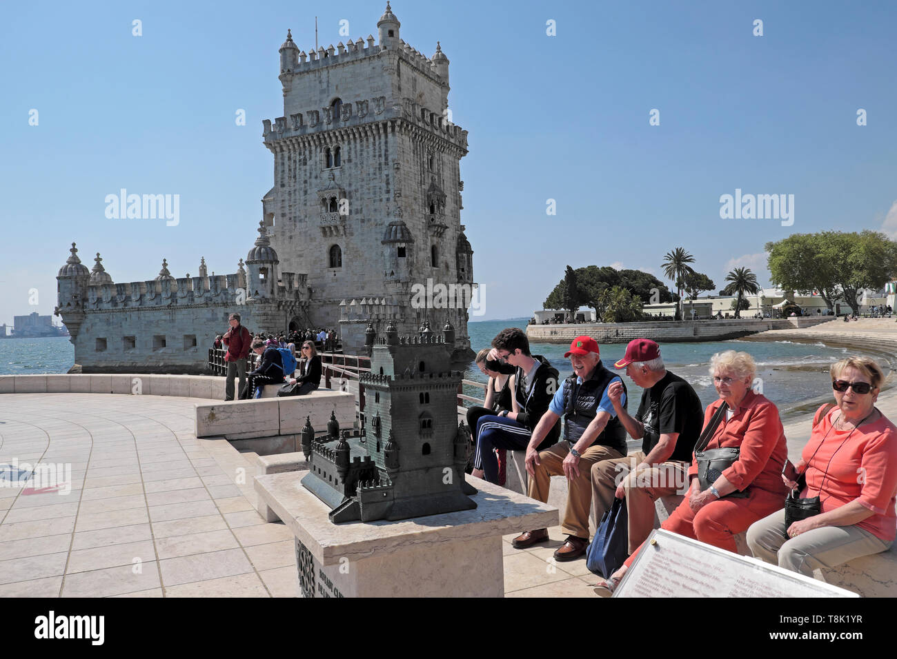 Seniors tourists people couples visiting Belem Tower sitting outside by a miniature model replica of building in Belem Lisbon Portugal  KATHY DEWITT - Stock Image