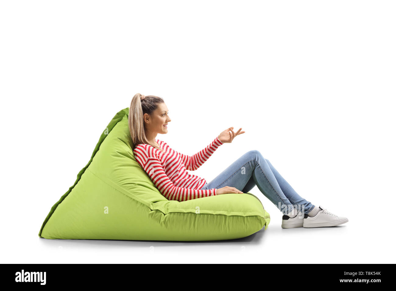 Full length profile shot of a young woman sitting on a bean bag and gesturing with hand isolated on white background - Stock Image