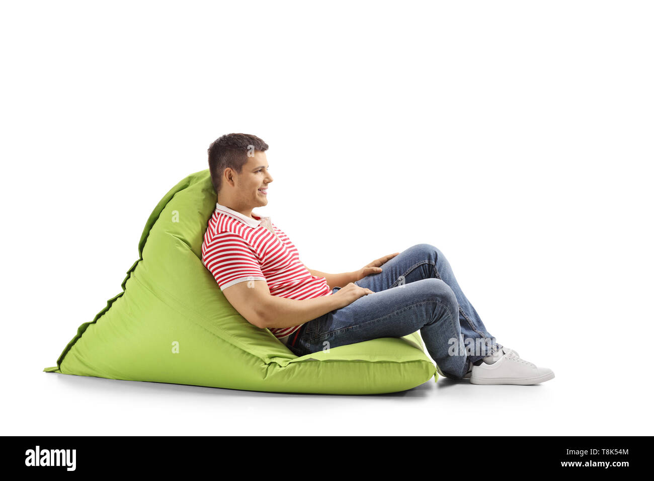Full length profile shot of a young man sitting on a green bean bag and smiling isolated on white background - Stock Image