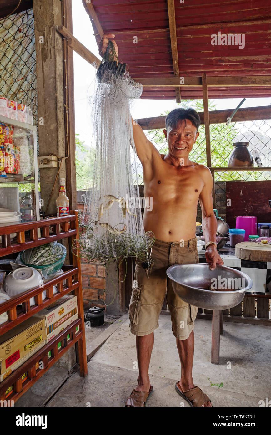 Laotian Fisherman Holds Up His Catch - Stock Image