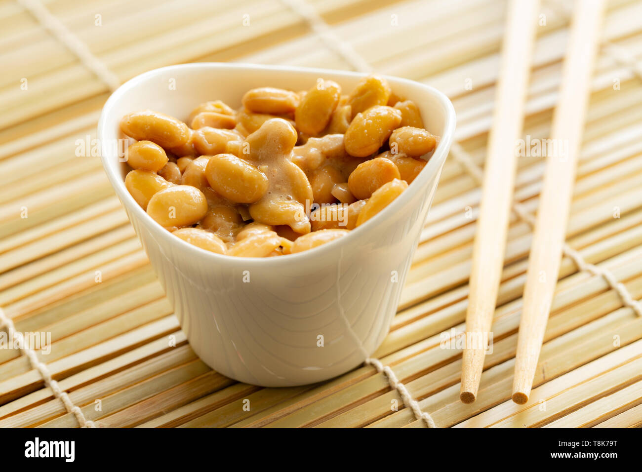 Eating healthy traditional japanese fermented soybeans called natto with chopsticks Stock Photo