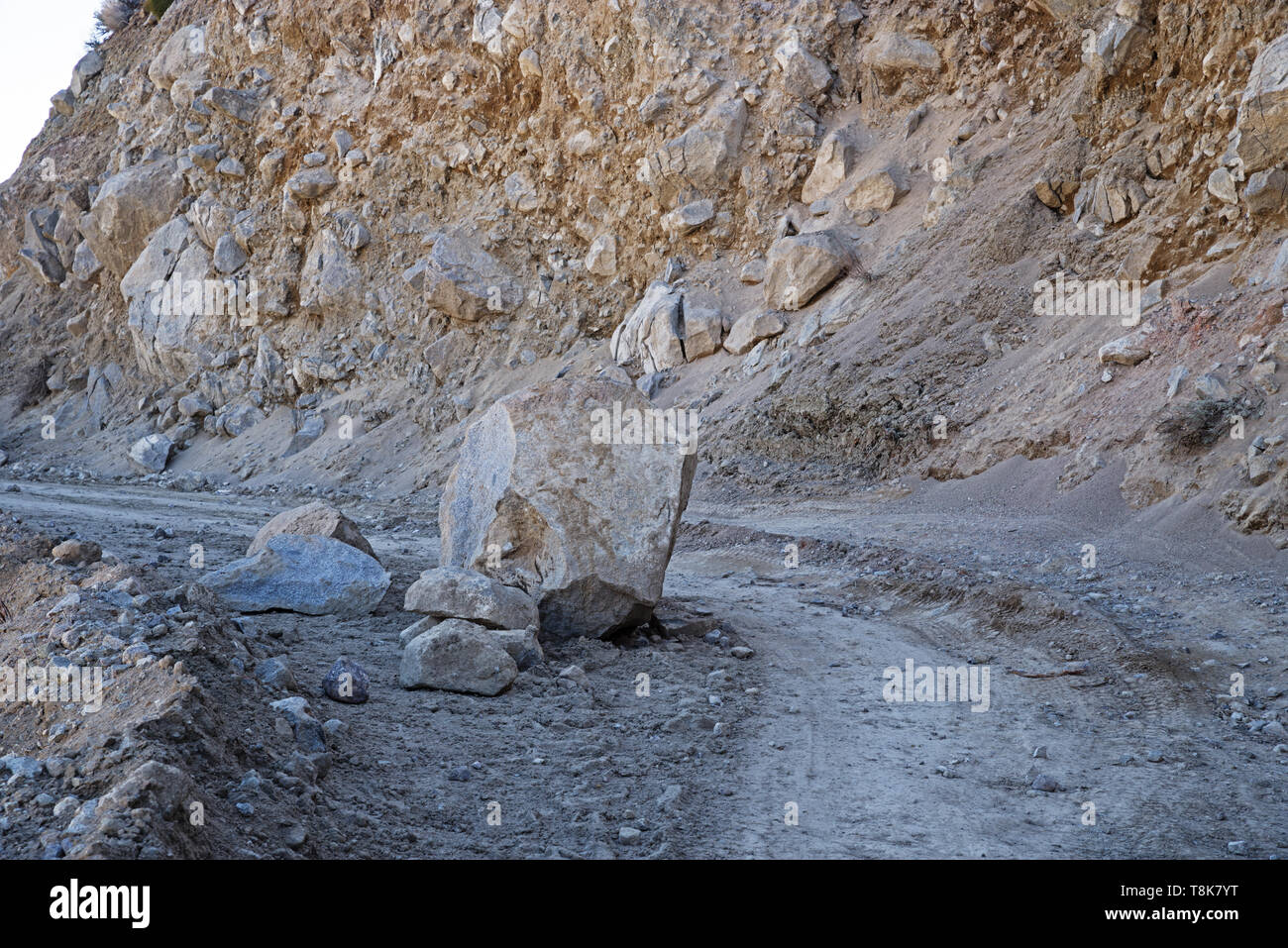 boulder that fell onto a dirt road along a very loose roadcut - Stock Image