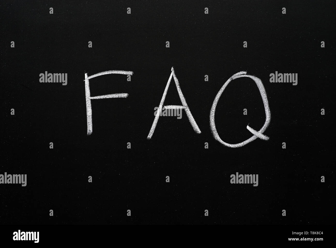 FAQ written on a blackboard in white chalk - Stock Image