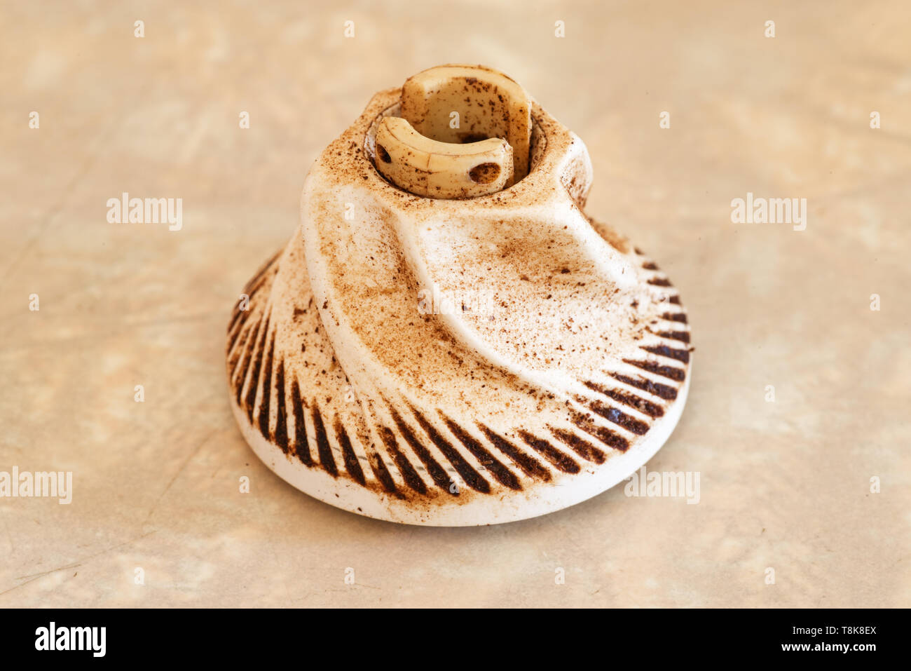 close up image of worn ceramic coffee grinder blade - Stock Image