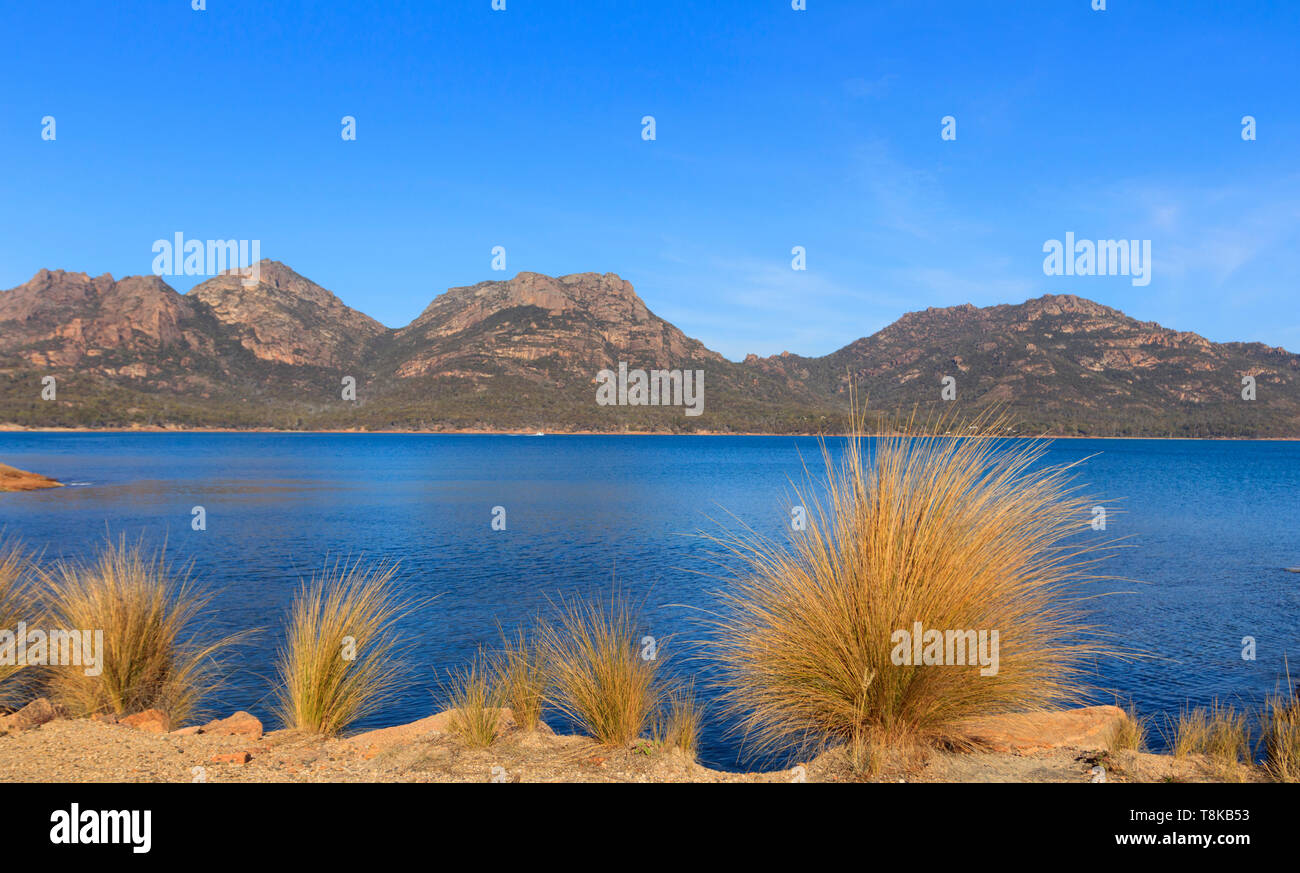The Hazards of Freycinet Peninsular viewed across Coles Bay with blue water and sky and copy space. - Stock Image