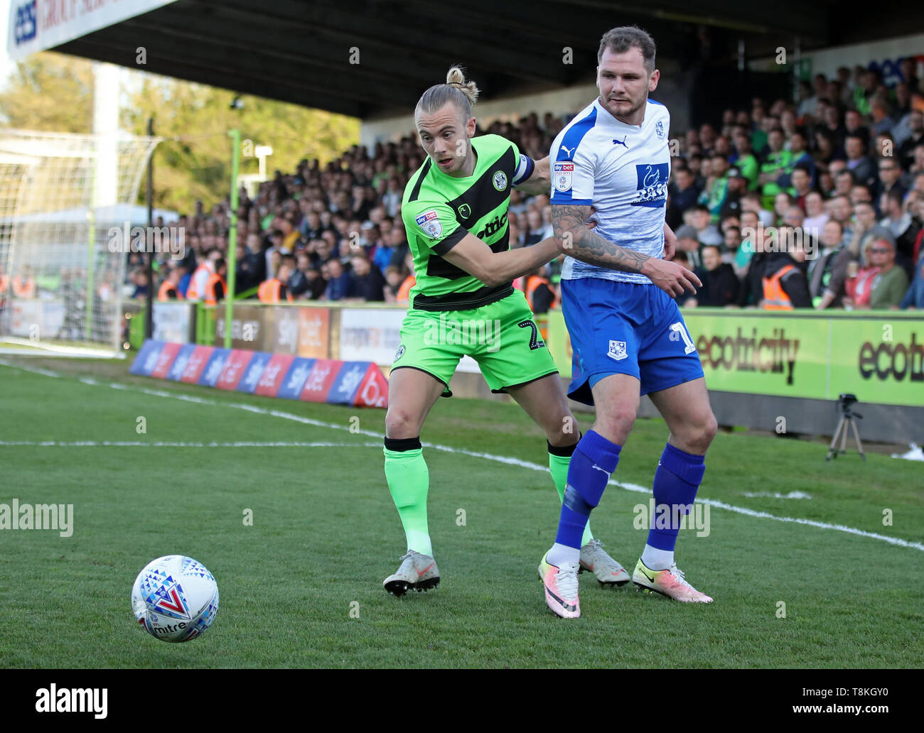 Forest Green Rovers' Joseph Mills and Tramere Rovers' James Norwood (right) battle for the ball during the Sky Bet League Two, Play-Off, Second Leg match at The New Lawn, Nailsworth. - Stock Image