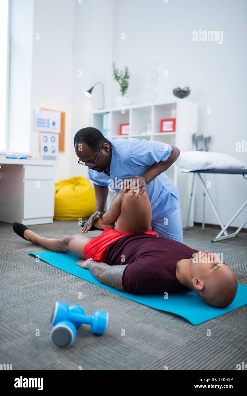 Bald sportsman lying on mat and having physical therapy for legs - Stock Image
