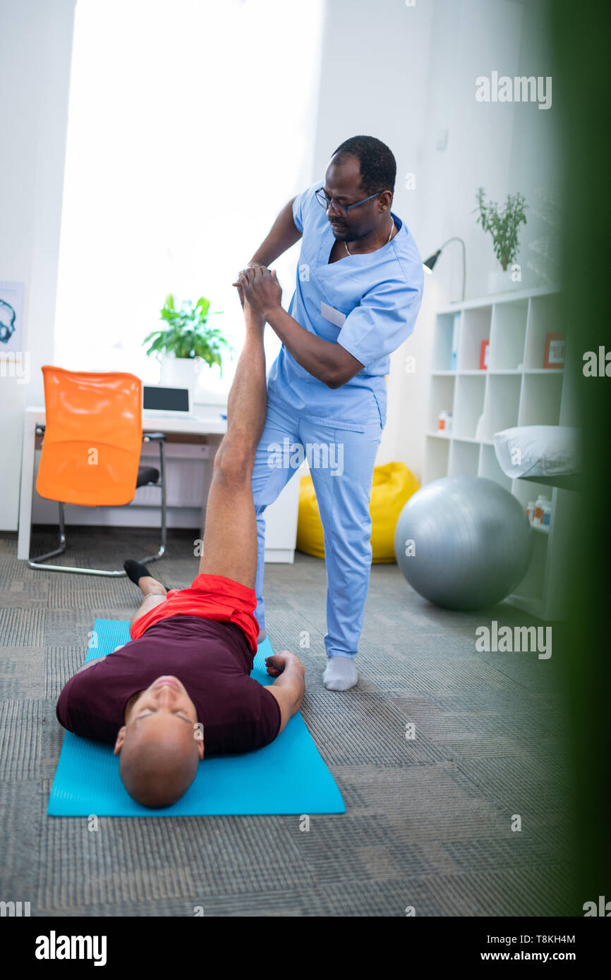 Sportsman lying on sport mat and having physical therapy - Stock Image