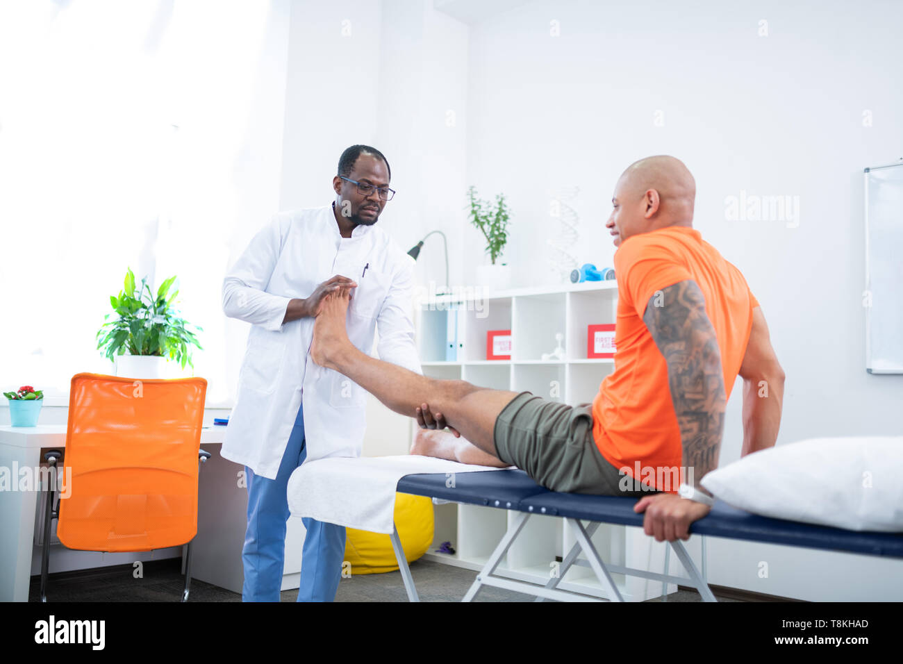 Tattooed sportsman smiling enjoying physical therapy for leg - Stock Image