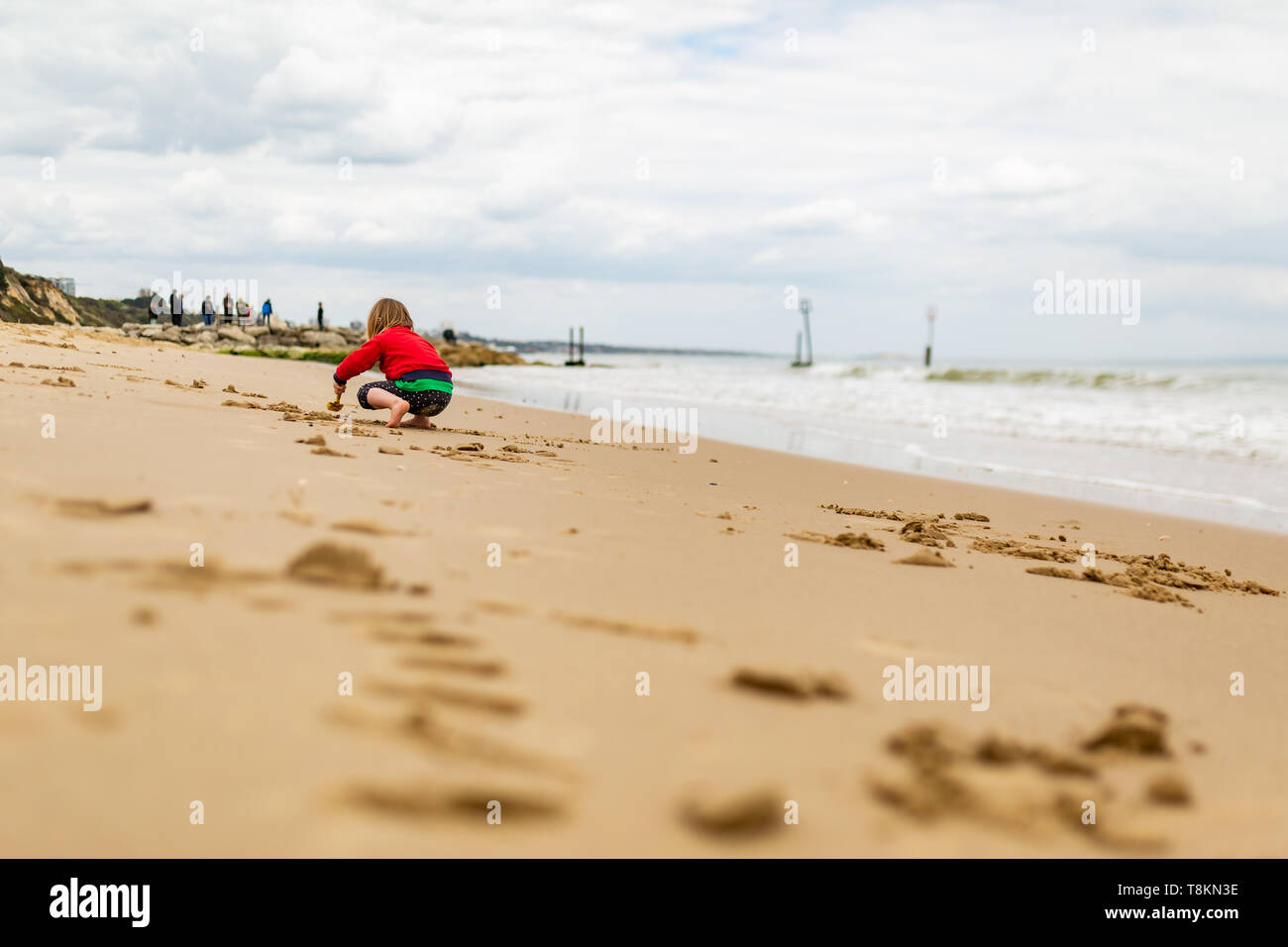 Young child crouching on beachs waters edge digging many small holes in sand, taken from behind. Poole, Dorset, England. Stock Photo