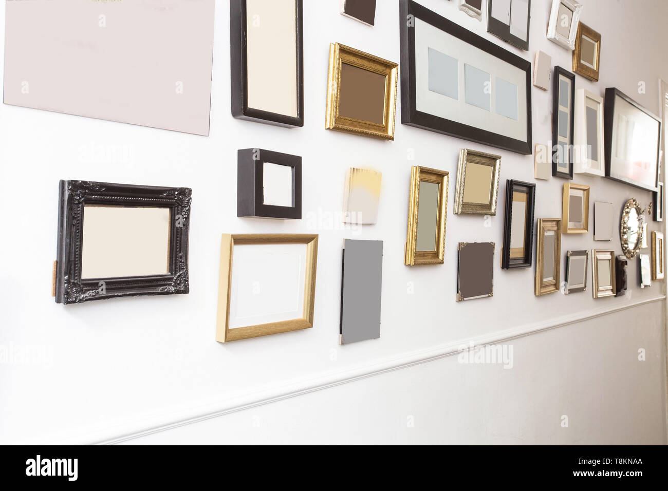 various many blank small picture frames on white wall, vintage retro design - Stock Image