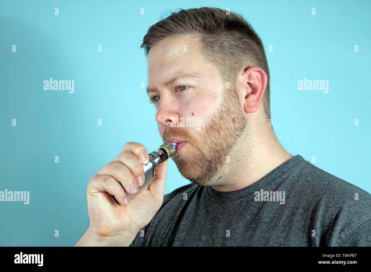 Young man vaping smoking an e-cigarette, he holds the vaporizer in his hand - Stock Image