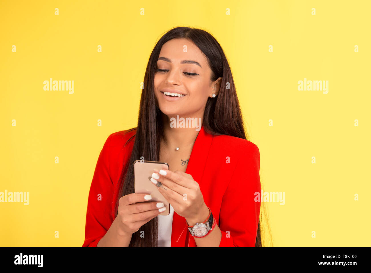 Joyful pretty African American female laughs at funny joke, surfing internet on mobile phone, reads good news, connected to wireless internet isolated - Stock Image