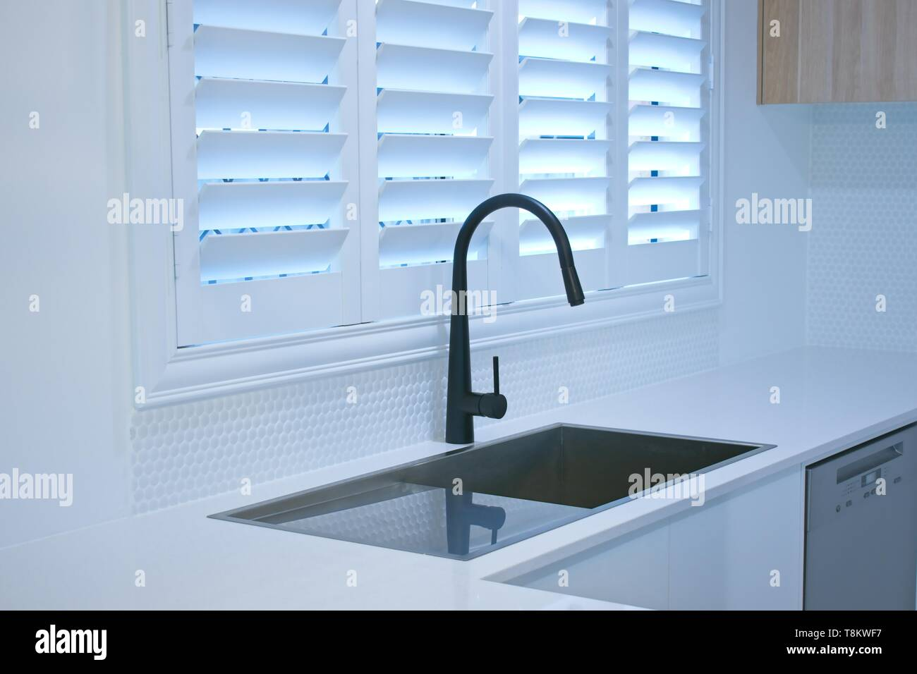 Open Plantation Shutters And Black Kitchen Sink Mixer Tap Stock Photo Alamy