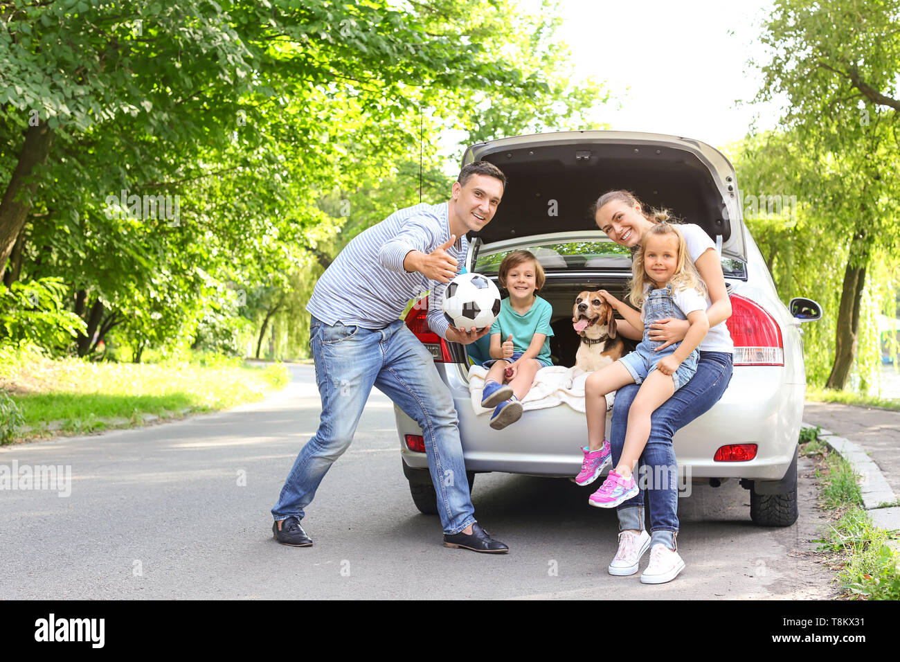 Happy family with cute dog near car outdoors - Stock Image