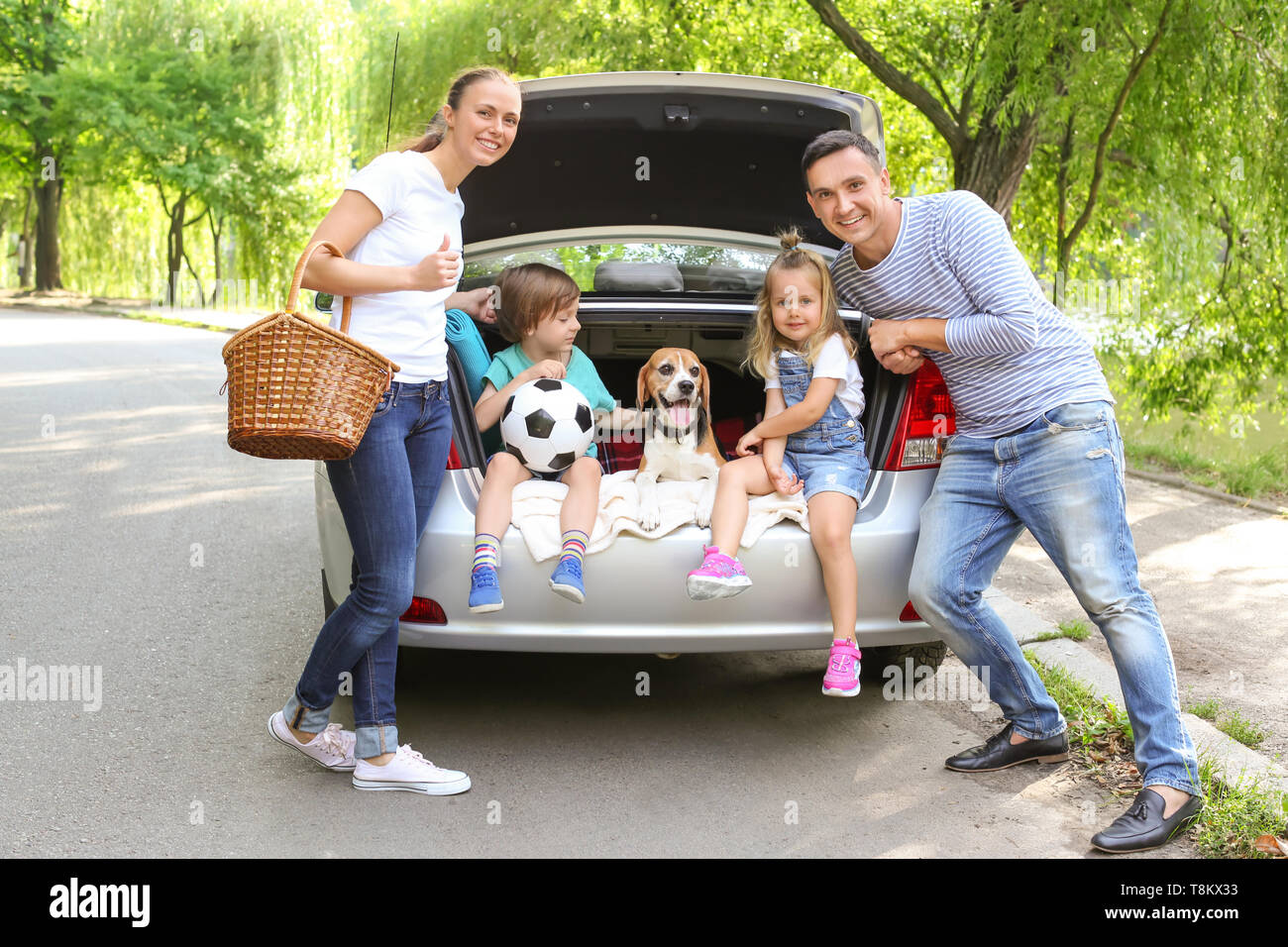 Happy family with beagle dog near car outdoors - Stock Image