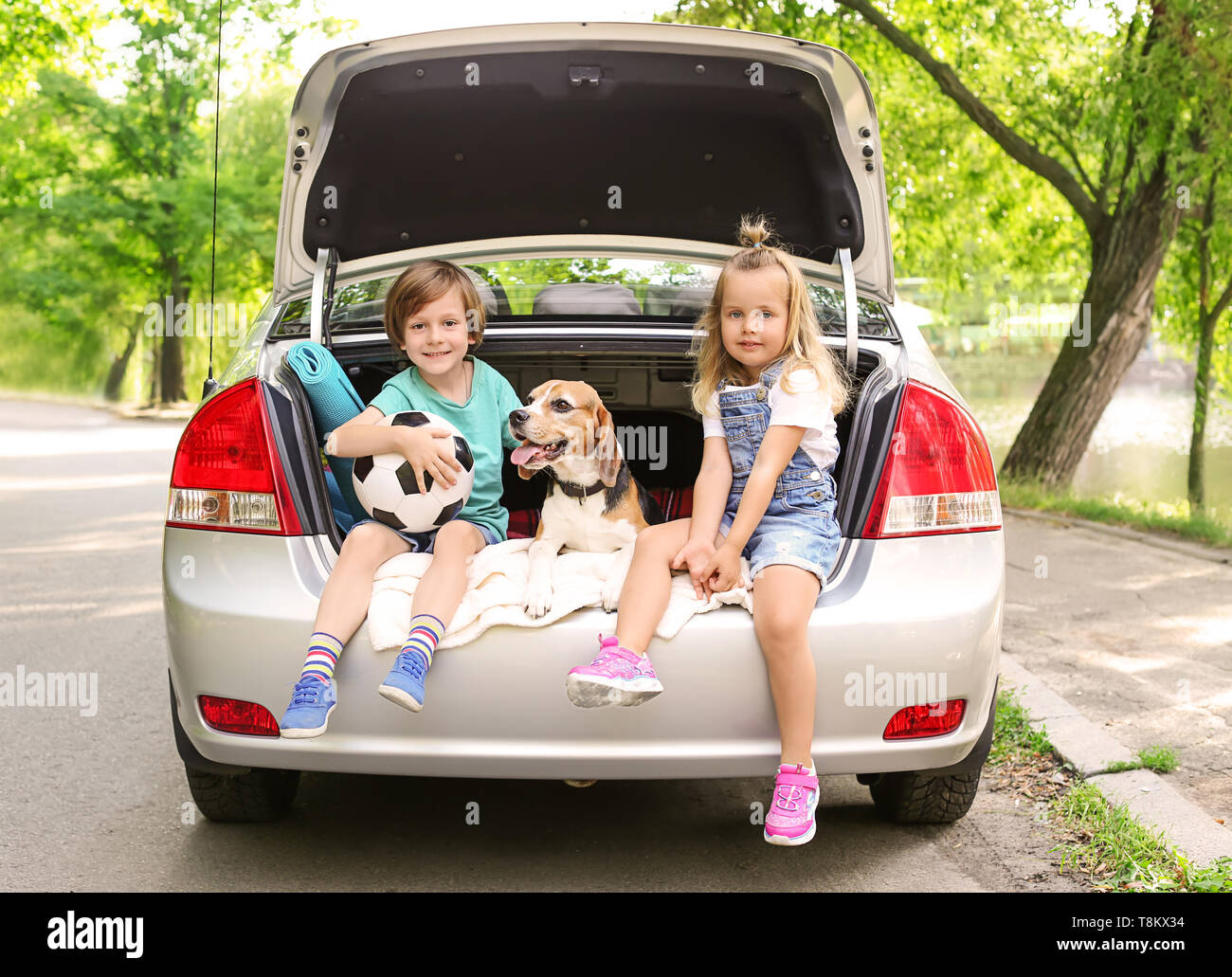 Cute children with dog sitting in car trunk - Stock Image