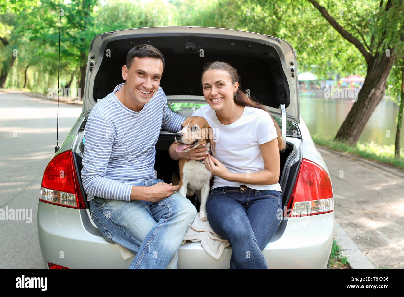 Young couple with cute dog sitting in car trunk - Stock Image