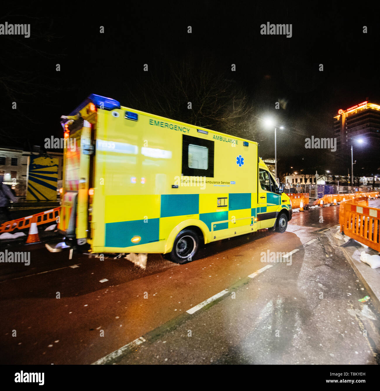 London, United Kingdom - Mar 5, 2017: Yellow NHS ambulance driving fast on the repaired with roadworks street in central london at night square image - Stock Image