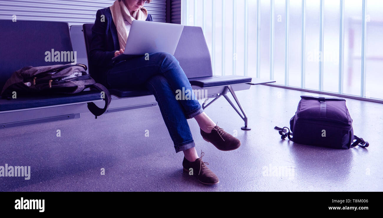 Casual dressed business woman working in empty airport terminal on thin laptop computer waiting for the delayed plane preparing working documents presentation - Stock Image