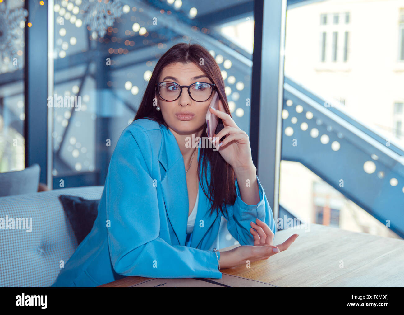 Closeup portrait of a beautiful woman shrugging shoulders puzzled while talking at phone. Hispanic girl wearing formal blue suit sitting at table in c - Stock Image