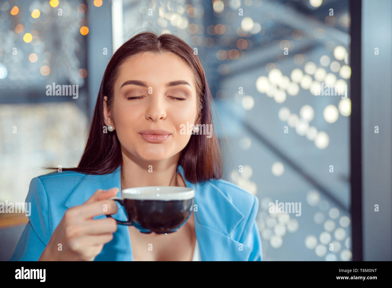 Love for coffee. Portrait of cute girl drinking enjoying her tea in the living room in manhattam apartment home or a fancy cafe, wearing blue suit, wh - Stock Image
