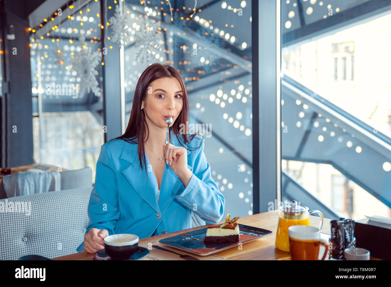 Woman licking spoon eating something delicious in a cozy restaurant and tastes local cuisine. Hispanic girl wearing formal blue suit sitting at a tabl - Stock Image