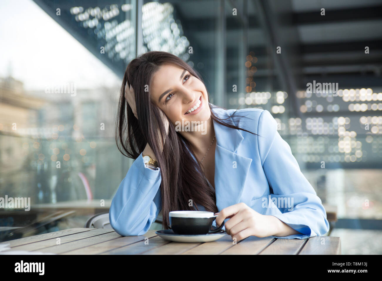 Daydreaming on a coffee break. Pensive happy woman remembering looking at side up sitting on terrace of bar coffee shop restaurant hoping thinking abo - Stock Image