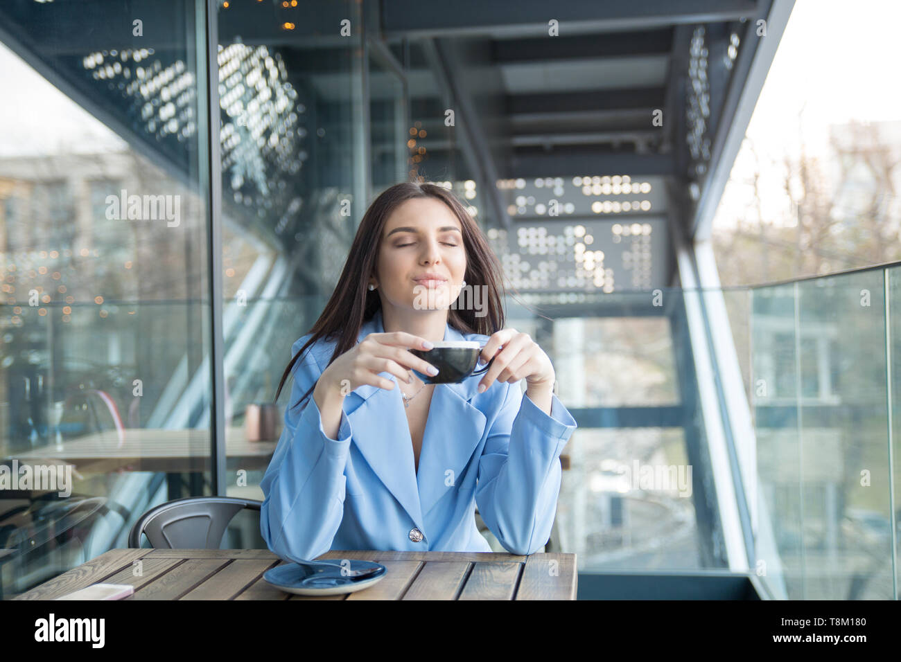 Love for coffee. Portrait of cute girl drinking enjoying her tea on the balcony over outside terrace with green bush background, wearing blue suit, wh - Stock Image
