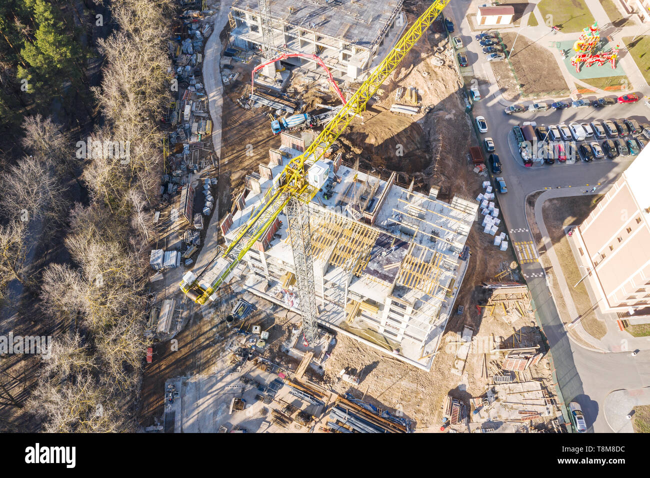 top view of city construction site with high yellow tower crane. developing of city infrastructure. drone photography - Stock Image
