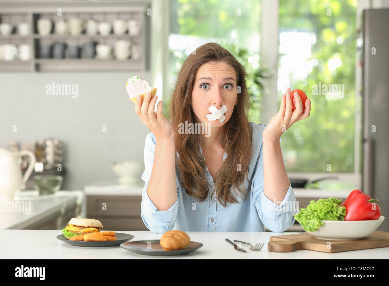 Stressful woman with taped mouth and different products in kitchen. Choice between healthy and unhealthy food Stock Photo