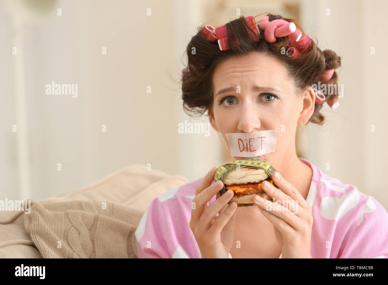 Stressful woman with taped mouth and tasty burger at home. Diet concept - Stock Image