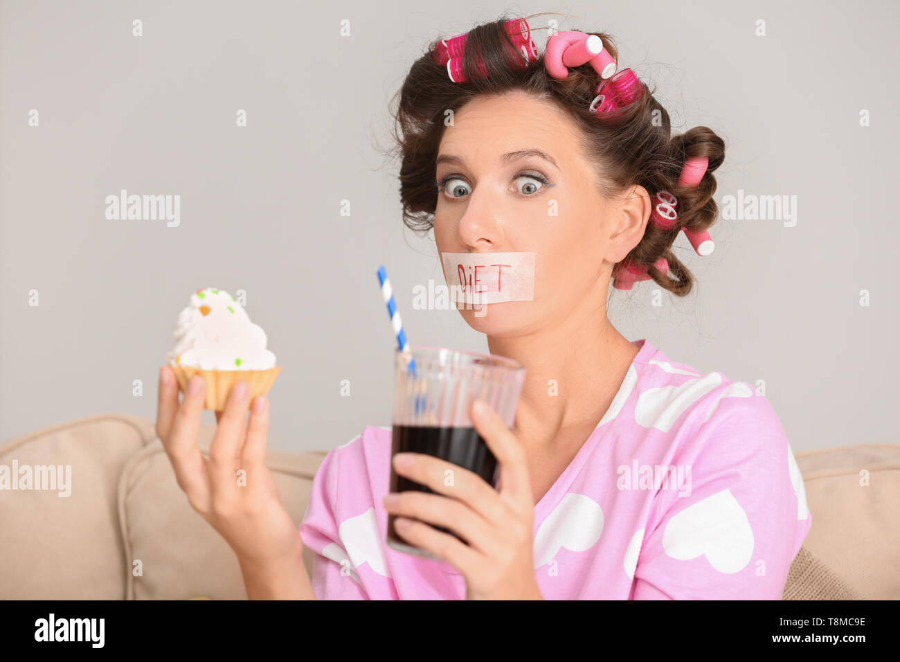 Stressful woman with taped mouth and unhealthy food at home. Diet concept - Stock Image
