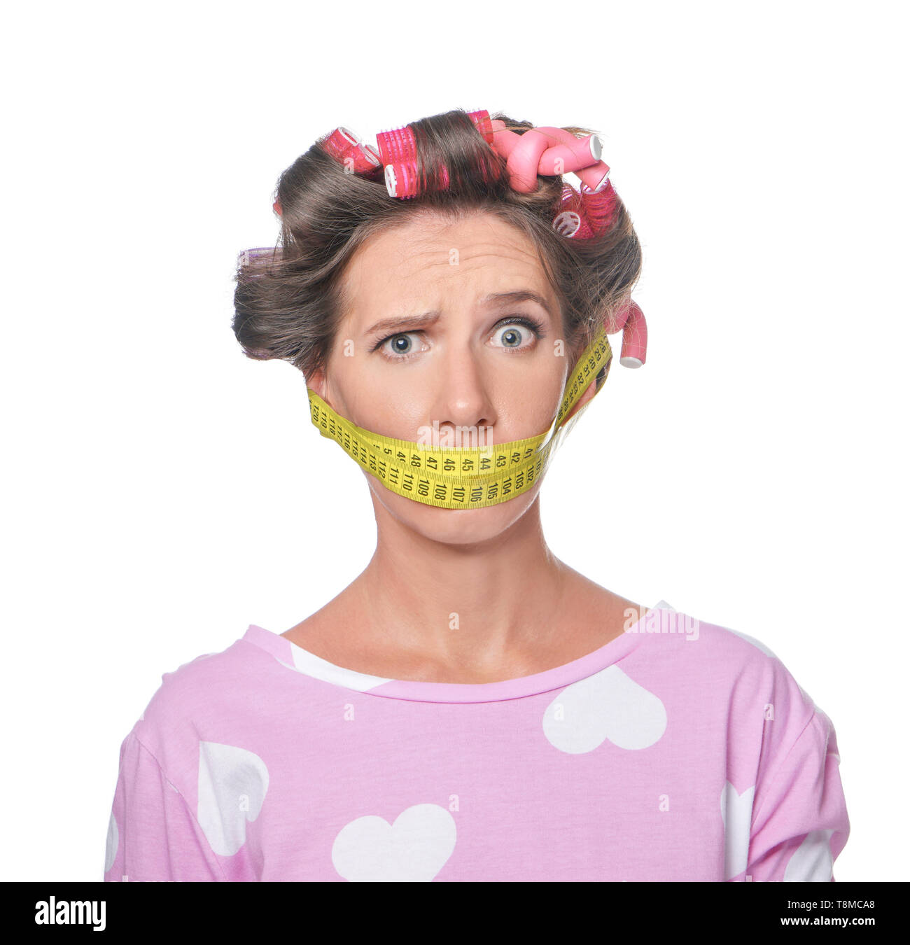 Stressful woman with measuring tape around her mouth on white background. Diet concept - Stock Image