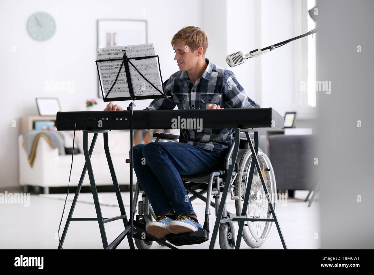 Young musician in wheelchair playing synthesizer at home - Stock Image