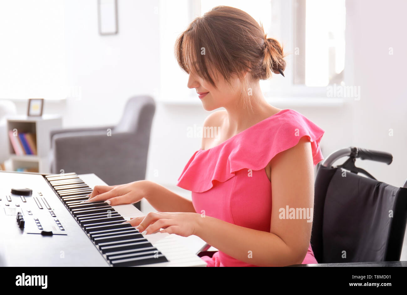 Beautiful young musician in wheelchair playing synthesizer at home - Stock Image