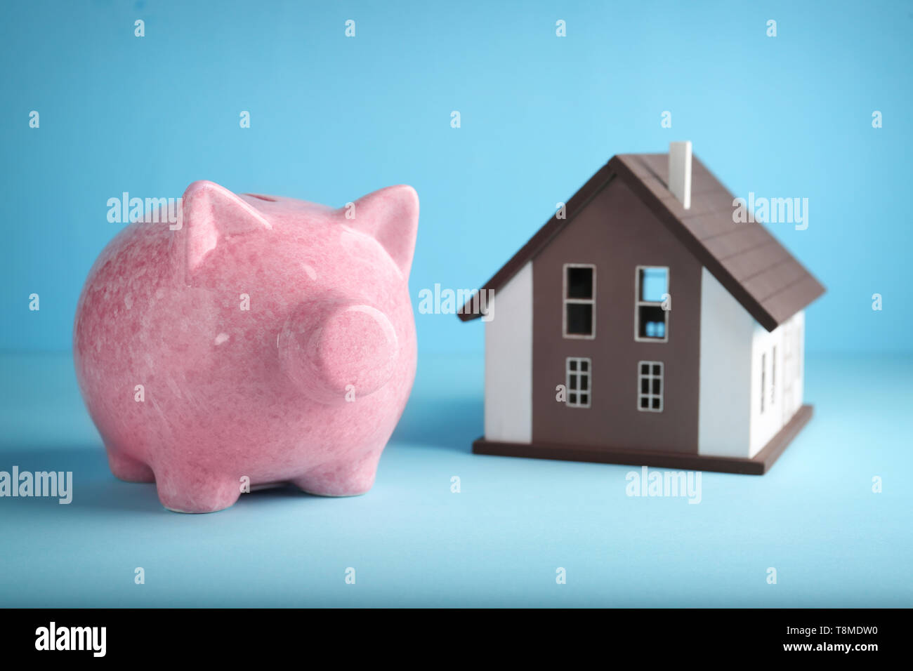 Cute piggy bank with house model on color background - Stock Image