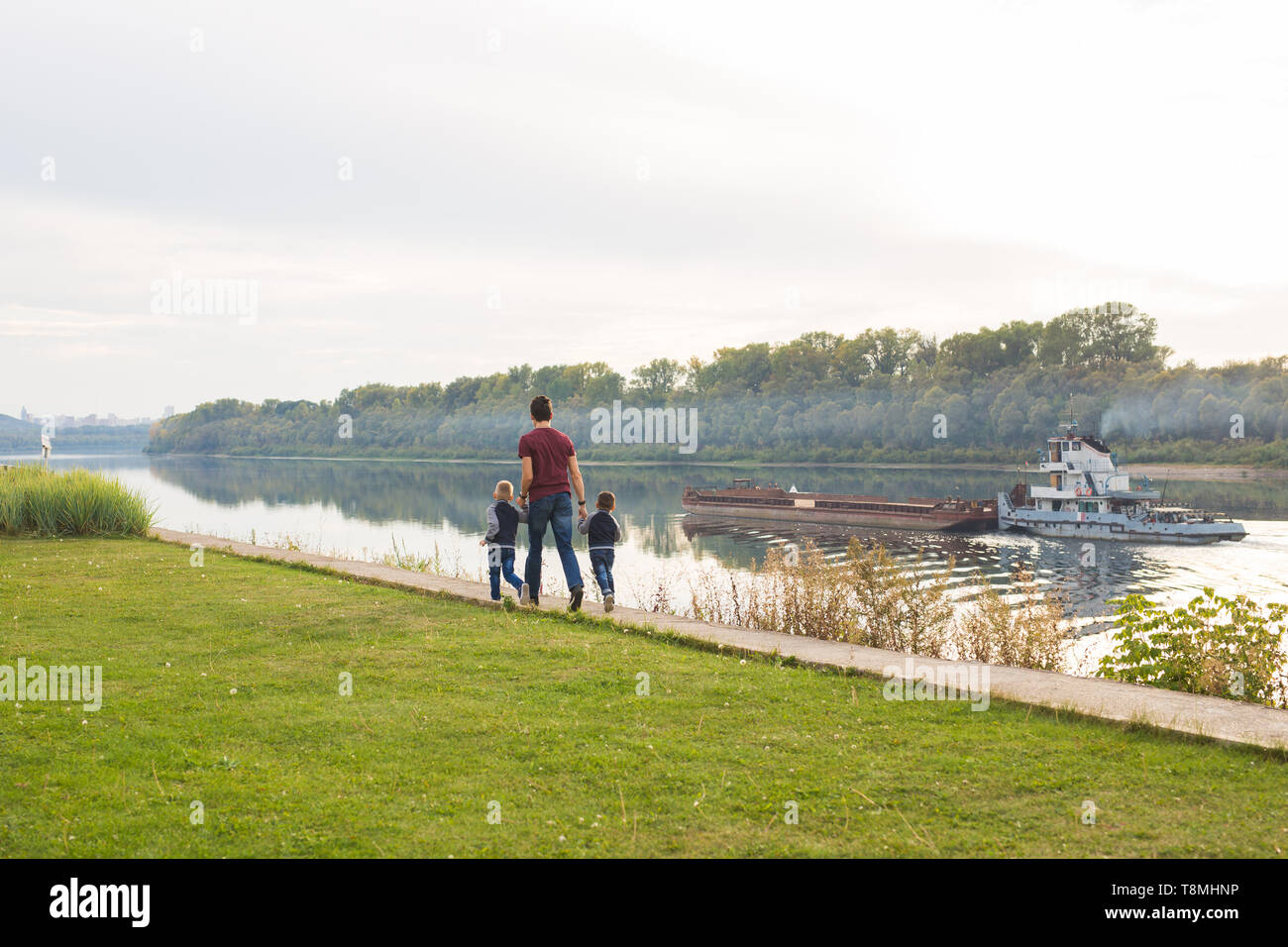 People and nature concept - Father walking with two boys by the water - Stock Image