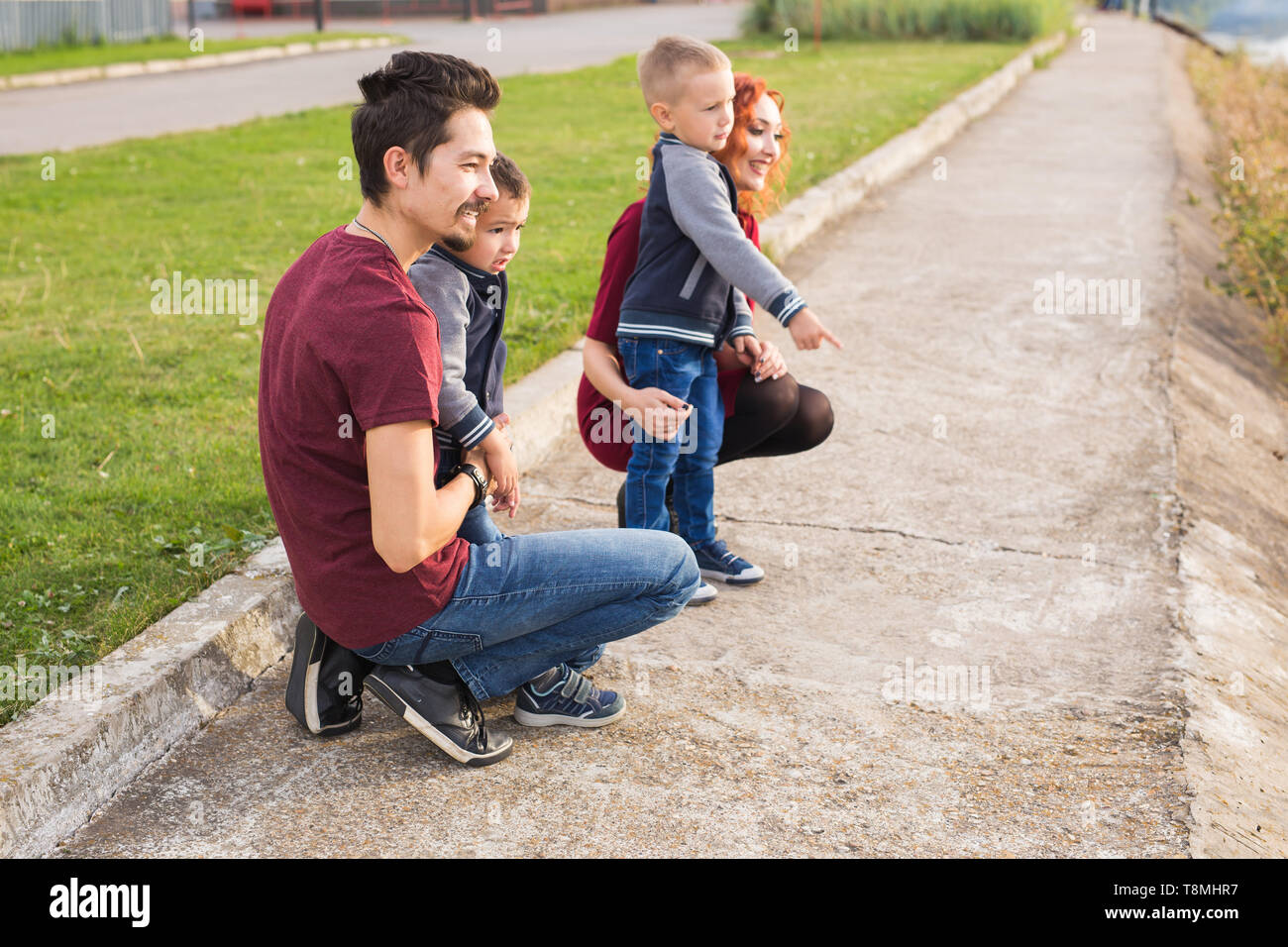 Parenthood, childhood and family concept - Parents and two male children walking at the park and looking on something - Stock Image