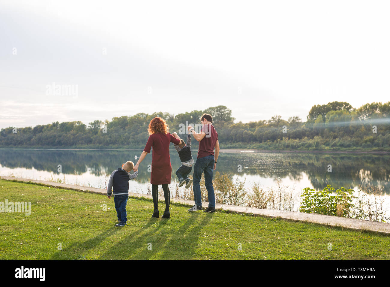 Parenthood and nature concept -Family of mother and father with two boys twins kids in a park at summer by a river at sunny day - Stock Image