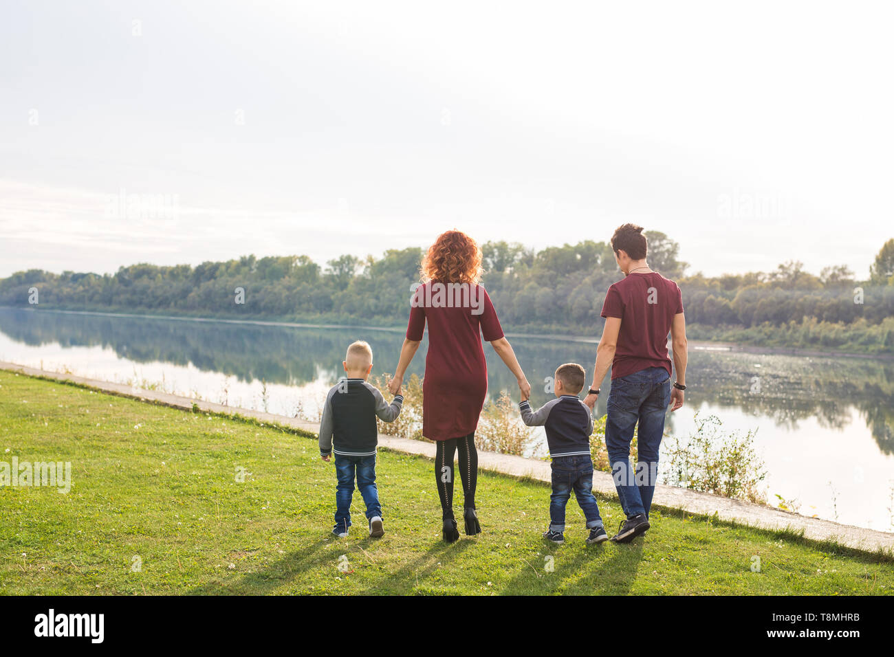 Parent, childhood and nature concept - Family playing with two sons by the water - Stock Image