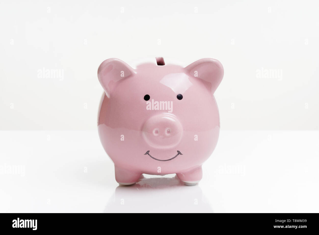 piggy or coin bank or piggybank or money box - finance and savings concept on white background with reflection - Stock Image