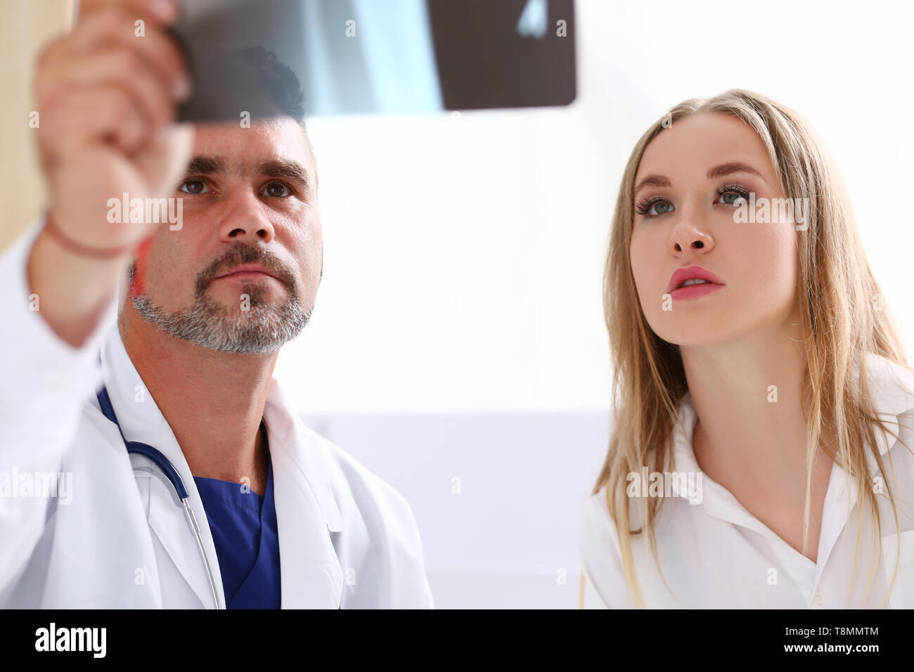 Mature male doctor hold in arm and look at xray photography - Stock Image