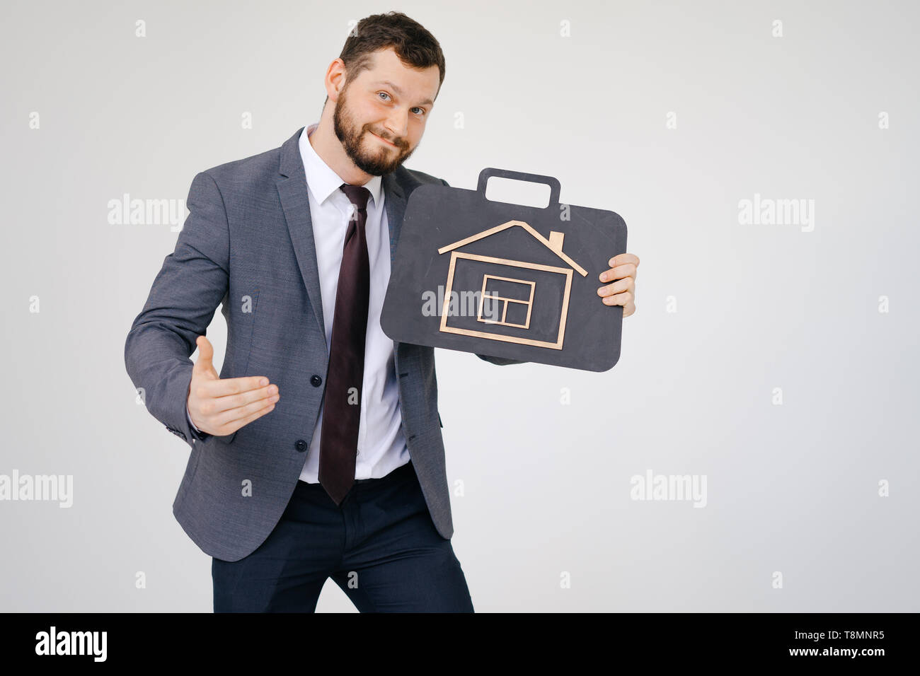 Businessman in suit portrait hold briefcase in hand - Stock Image