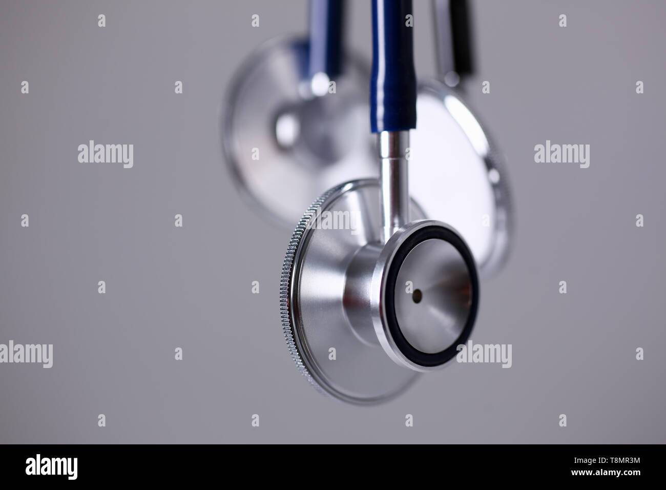 Stethoscope head lying on gray background closeup - Stock Image