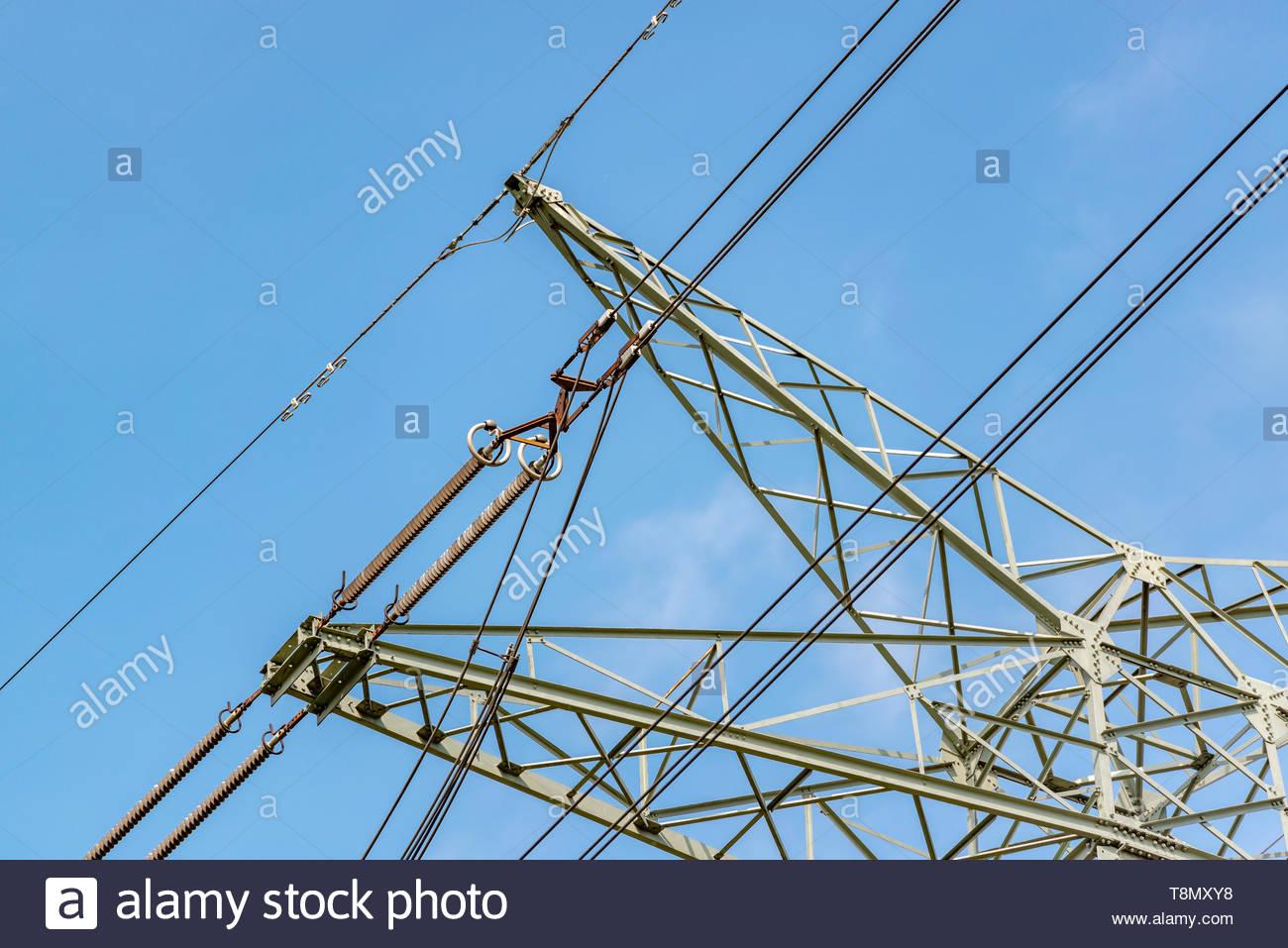 Detailaufnahme Hochspannungsmasten vor blauem Himmel - Stock Image