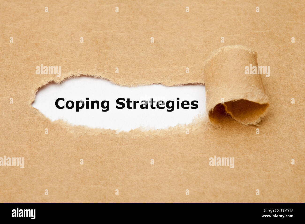 Text Coping Strategies appearing behind ripped paper. Concept about the series of behavioral and psychological skills and actions needed to handle str - Stock Image