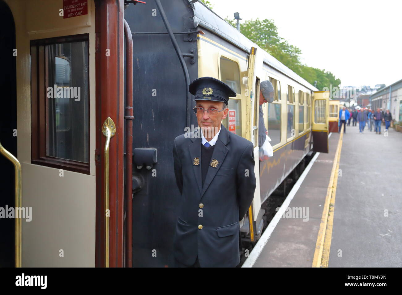 A conductor standing on the platform next to the British Railways steam train at Paignton station, Devon, UK - Stock Image