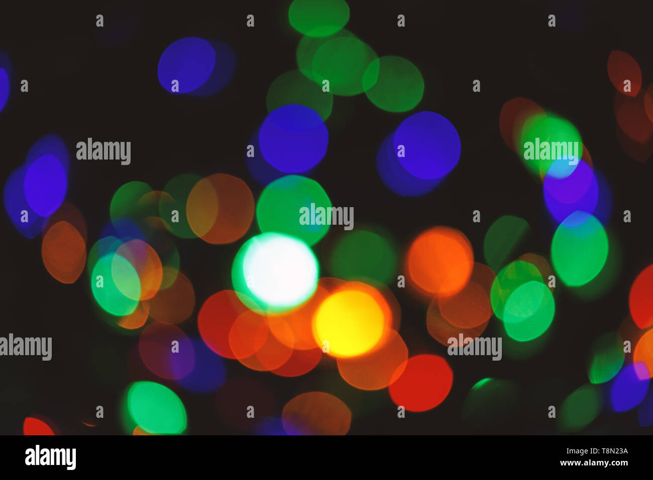 Christmas decorations concept. Defocused light of colorful garland. Festive backdrop with colorful lights. Bright and festive atmosphere of coming holiday. Abstract colorful bokeh background. Stock Photo