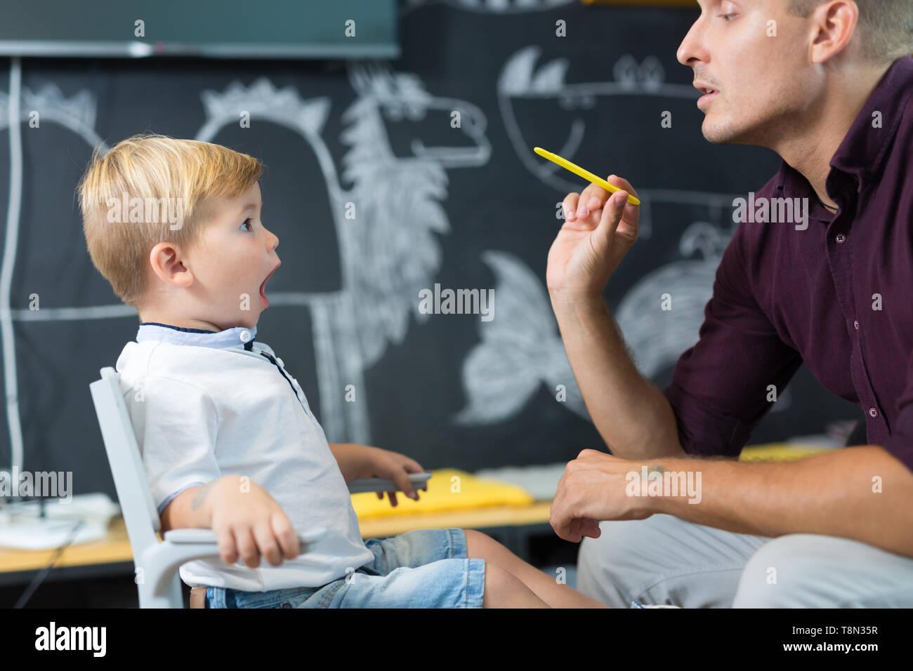 Cute little boy at speechtherapist session. - Stock Image